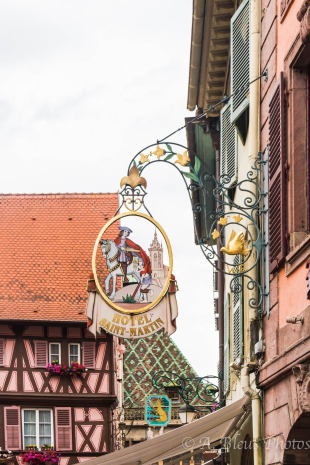 Those wrought iron signs are from a medieval tradition.  These signs or emblems are eye-catching and found in many old walking streets and in many other european regions.